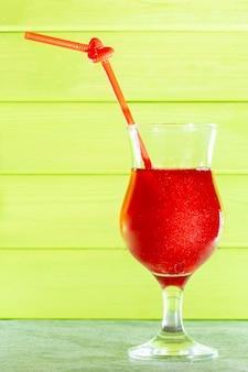 Коктейль с блестками. летний охлаждающий красный коктейль в стеклянном стакане с трубочкой