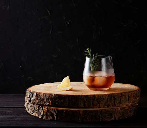 Cocktail with ice rosemary and lemon on wooden table