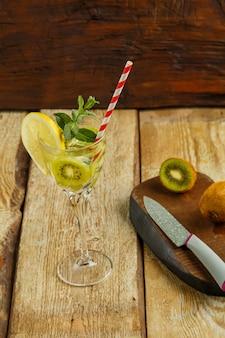 Коктейль с мятой и лимоном киви в стакане на деревянном столе рядом с лимоном и киви на доске