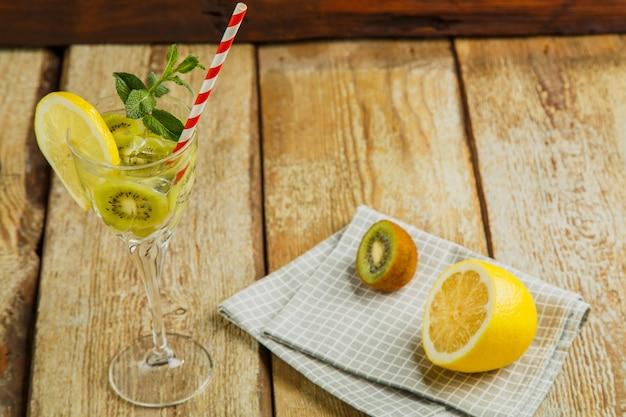 Коктейль с мятой и лимоном киви в стакане на деревянном столе рядом с лимоном и киви на салфетке