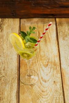 Коктейль с мятой киви и лимоном в стакане на деревянном столе