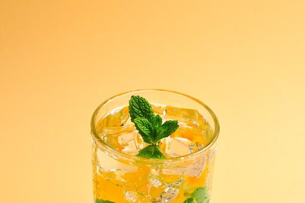 Коктейль с лимоном и мятой на бежевом фоне. скопируйте пространство.