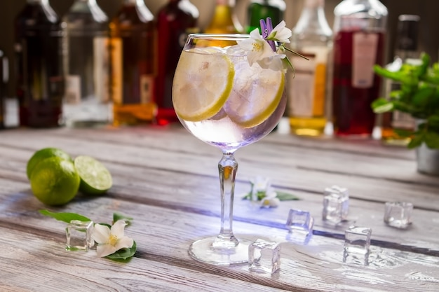Коктейль с лимоном в стакане. белые цветы и кубики льда. том коллинз работал в ночном клубе. алкогольный напиток с лучшим джином.