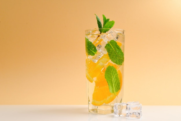 Cocktail with lemon and mint on a beige surface