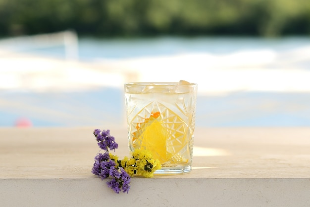 Cocktail with lemon and mint in a glass. with flower decor