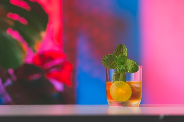 Cocktail with lemon slice and mint leaves