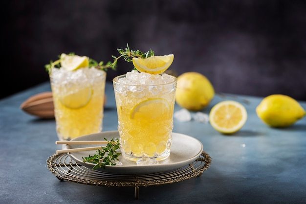 Коктейль с лимоном, тимо и колотым льдом на темном фоне, концепция бара и изображение выборочного фокуса