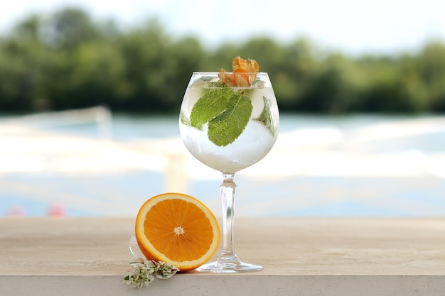 Cocktail with mint and ice in a glass tumbler. with flower and fruit decor