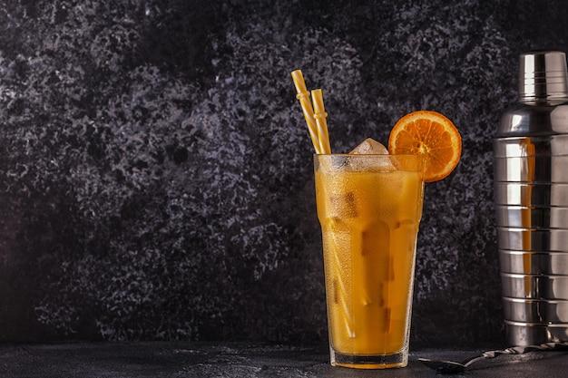 Коктейль с апельсиновым соком и кубиками льда, выборочный фокус.