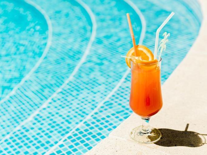 Коктейль с дольками апельсина и соломкой у бассейна