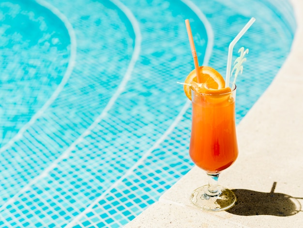 Cocktail with orange slices and straws placed on poolside