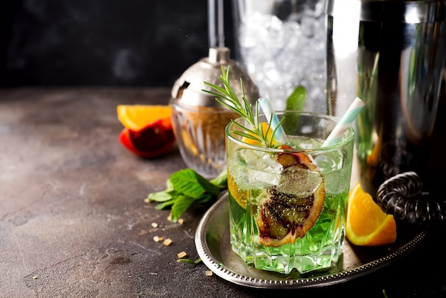 Cocktail with red lemon mint and vodka on dark stone background