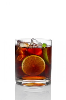 Cocktail with rum and cola with ice, lime and lemon in oldfashioned glass isolated on white