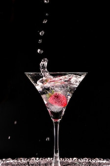 Cocktail with strawberries isolated on black background. glass of vodka splashing.