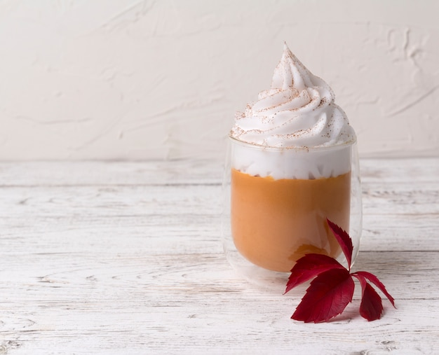 Cocktail with whipped cream on top on white wooden background