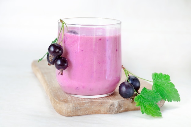Cocktail of yogurt with black currant berries in a glass on a wooden board.
