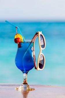 Разноцветные коктейли с фруктами и солнцезащитные очки на пляже