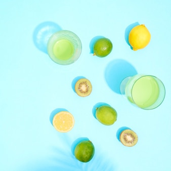 青の背景にライムとレモンをグラスに入れたカクテル。