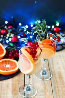 柑橘系の果物、赤スグリ、シナモンスティック、緑のローズマリーをワイングラスに入れたカクテル。