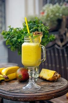 Коктейли с ананасом, бананом и манго на деревянном столе