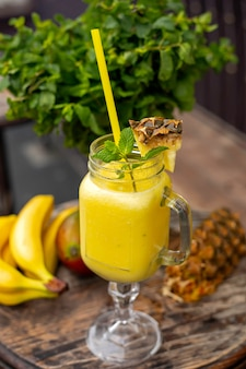 Cocktails with pineapple, banana and mango on a wooden table