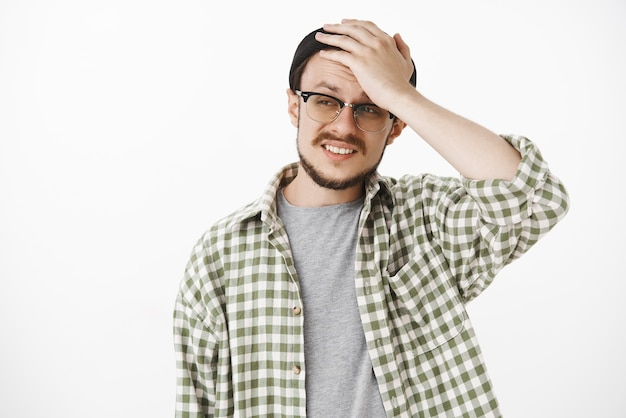 Cocnerned and troubled upset guy with beard and moustache in black hipster beanie and glasses holding hand on head frimacing and frowning stucking in troubled and perplexing situation