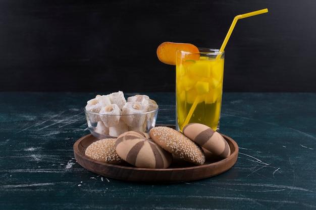ココアとバニラのクッキーパン、ロクムと木製の大皿にジュースのガラス