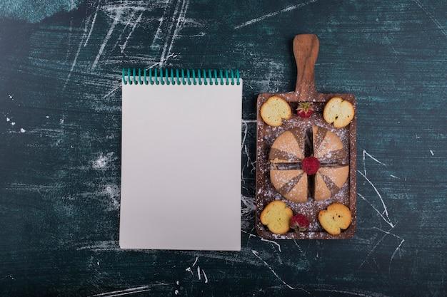 ノートブックを脇に木の板にココアとバニラのクッキー