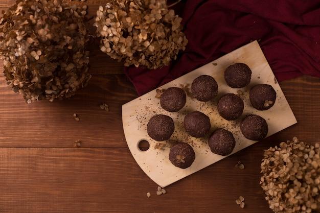 Какао шарики, шоколадные трюфели торты на борту на деревянный стол