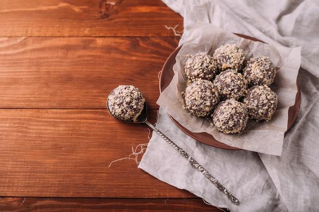 ココアボール、チョコレートトリュフケーキ、ボード上の木製テーブル