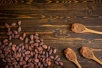 Cocoa beans and cocoa powder in wooden spoon on old natural wooden background
