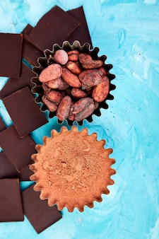 Cocoa beans on blue table. dark chocolate pieces