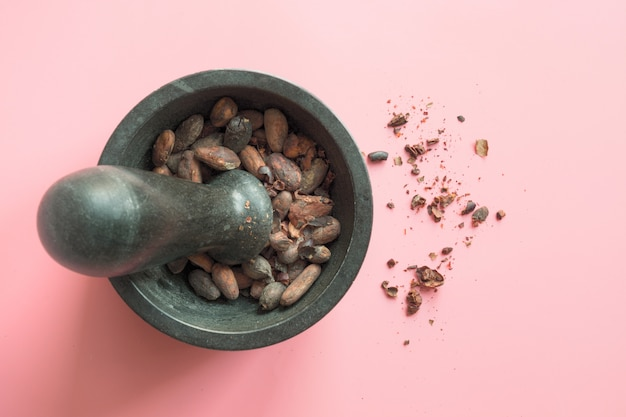 Cocoa beans in bowl on pink.