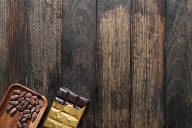 Cocoa beans and chocolate bar on wooden background