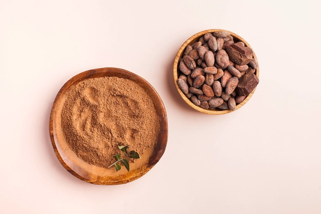 Cocoa beans, cocoa powder on a pink surface