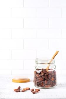 軽い台所のテーブルの上のガラス瓶の中のカカオ豆。伝統的なチョコレートを作るための料理の調理壁。セレクティブフォーカス。