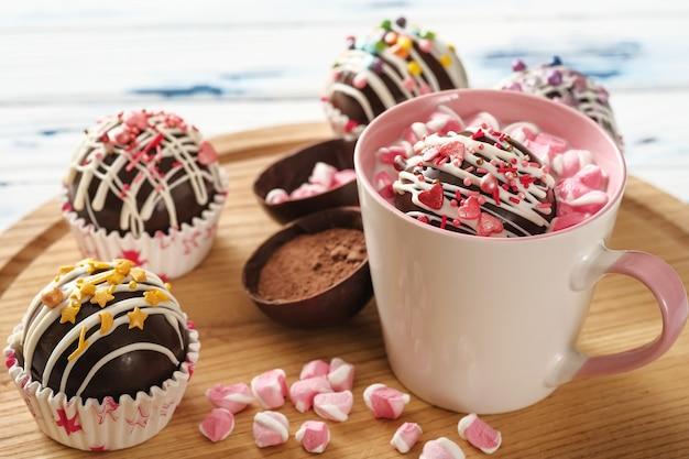 Какао-бомбы - это скорлупа из черного шоколада, наполненная какао-порошком и зефиром.
