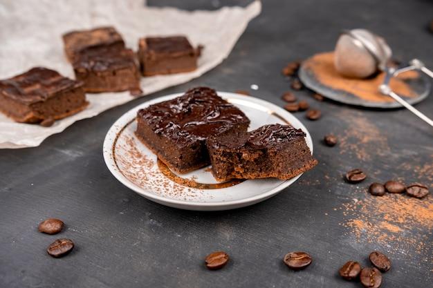 Какао-брауни залить растопленным черным шоколадом, разрезанным на квадратные кусочки на белой тарелке.
