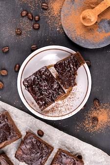 Какао-брауни залить растопленным черным шоколадом, разрезать на квадратные кусочки. плоский вид сверху