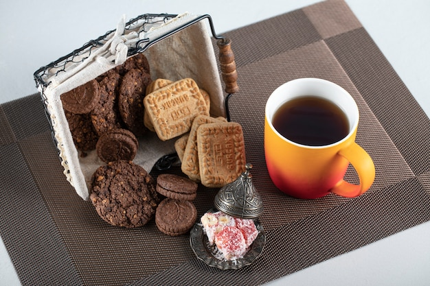 Cocoa and butter biscuits in a basket with a cup of tea