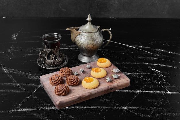 Biscotti al cacao e burro su una tavola di legno con tè.