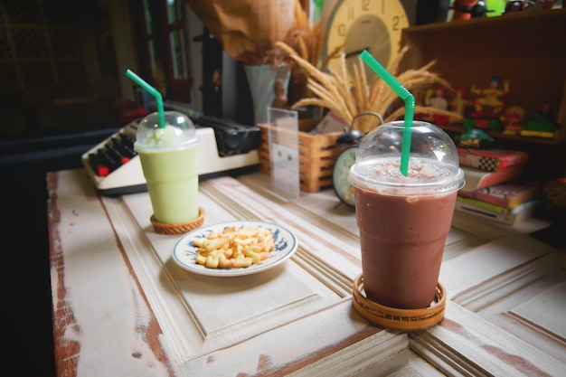 Cocoa, chocolate and green tea milk frappe and alphabet cookies on wood shelf.