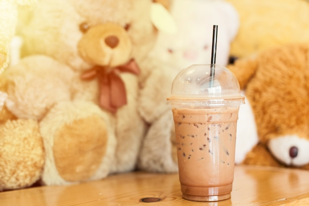 Cocoa cold with ice in the cup with straw put it on the wood table with bear doll in the cafe
