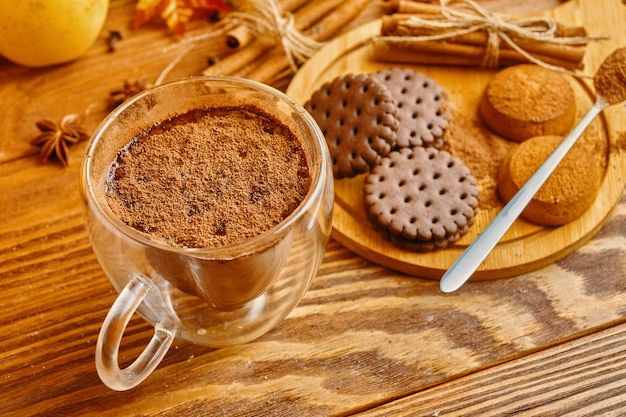 はがきの秋の装飾が施された木製のテーブルの秋の構成にココアクッキーとシナモンスティック...