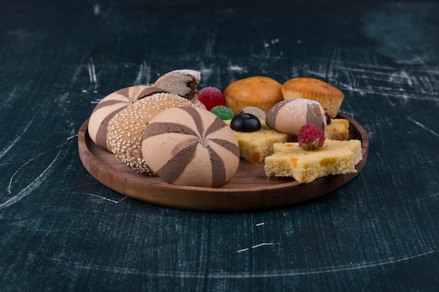 Cocoa cookies and buns with berries on a wooden platter
