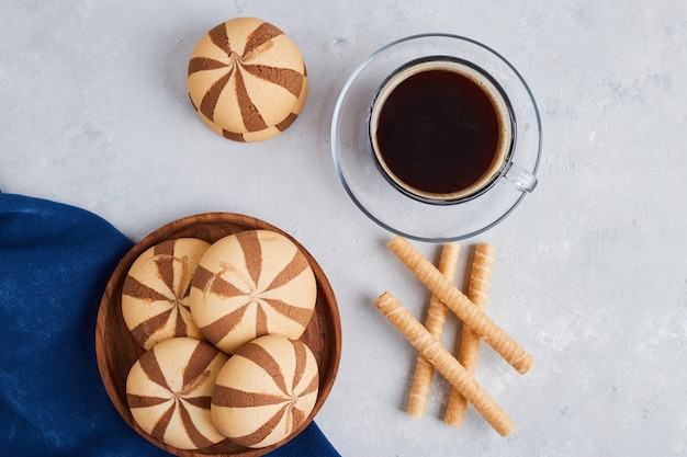 Cocoa cookies with a cup of coffee on white surface, top view.