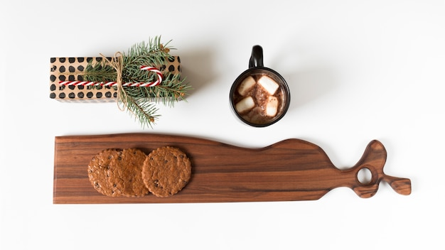 Cocoa cup near wrapped gift and board with cookies
