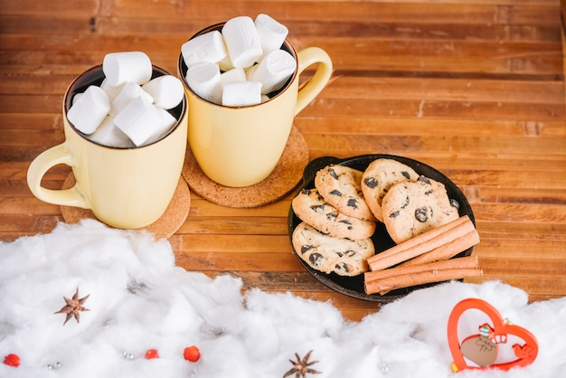 Cocoa cups with marshmallows and plate with cookies