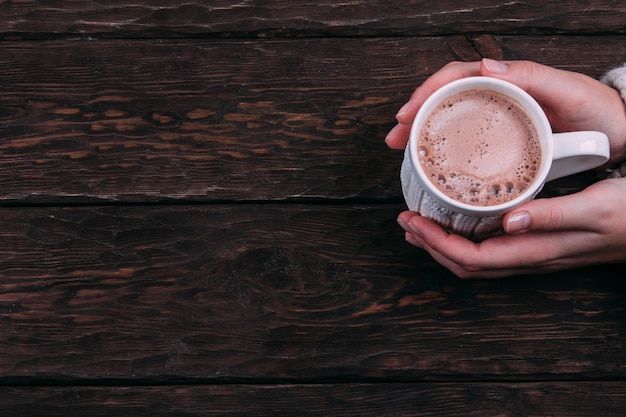 Cocoa in the hands on a wooden background