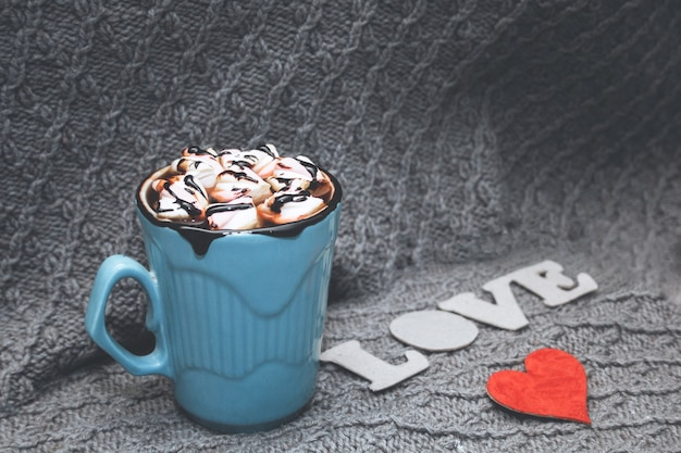 青いマグカップのココア、loveの文字、灰色のニットの背景に小さな赤いボール紙のハート